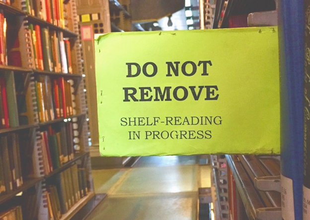 "Photograph of a sign in the stacks that says, ""Do Not Remove, Shelf-Reading In Progress."" by Brandon Harrington, at the Burke Library at Union Theological Seminary (2018)."