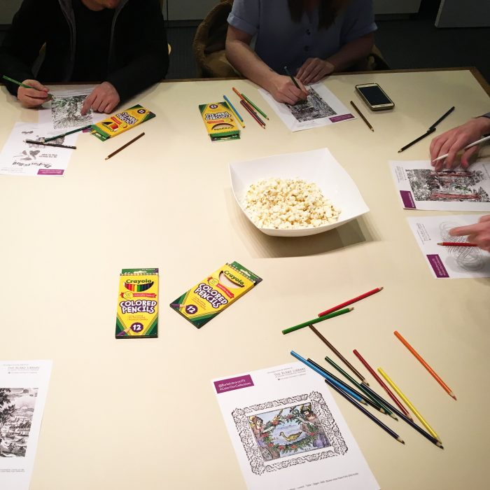 Photograph from the Color Our Collections 2019 coloring event at the Burke Library at Union Theological Seminary, Columbia University. Image shows a table with popcorn and people's hands holding pencils and coloring in images on paper