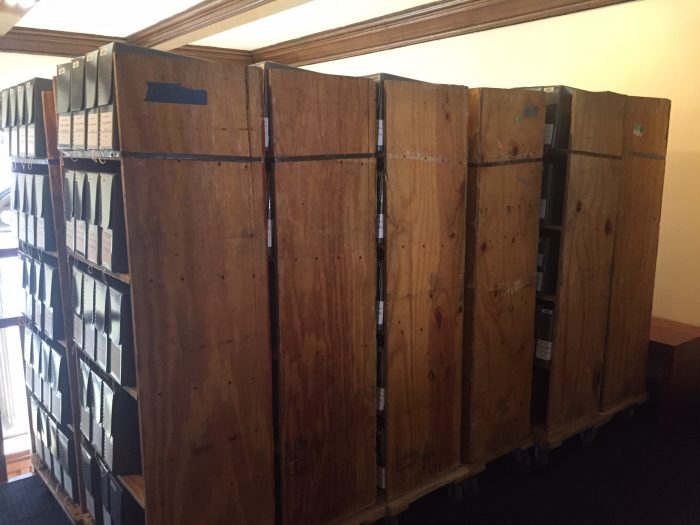 Large wooden shelving units on wheels, each containing about twenty archive storage boxes, at the Burke Library