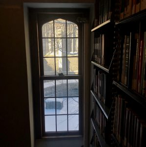 """Photograph by Hannah Ervin, of a window seen from inside the Burke Library book shelving area, looking out onto the Union Theological Seminary quadrangle (""""the quad"""") with visible construction scaffolding along the exterior walls"""