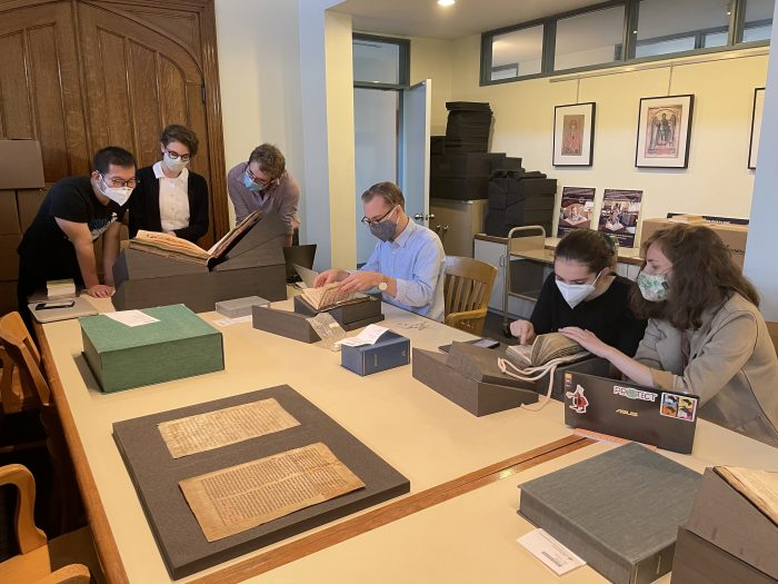 Students wearing face masks examine books and yellowed manuscript pages in a warmly-lit conference room