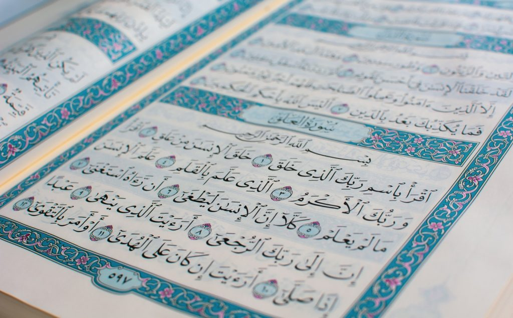 blue and white arabic writing on page from Q'uran