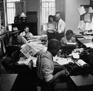 African American women and men in a newsroom with typewriters and newspapers on desks