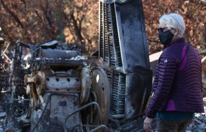 Felicia Rice looking at the burnt remnants of Moving Parts Press