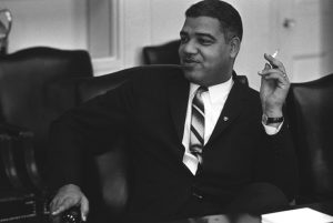 African American man in 1960s era suite and tie sitting in White House smoking a cigarette