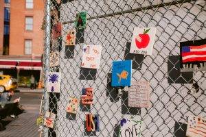 handmaid cards and messages affixed to chainlink fence